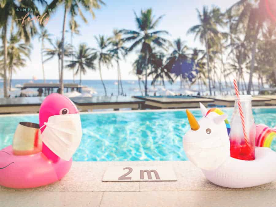 Summer activities for families Inflatable pool toys at tropical resort pool wearing face masks staying 2 meters aside to keep social distance during COVID-19 pandemic. Concept of travel industry difficulties during summer 2020