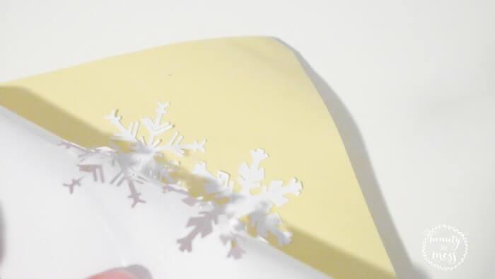 peeling snowflakes off adhesive paper