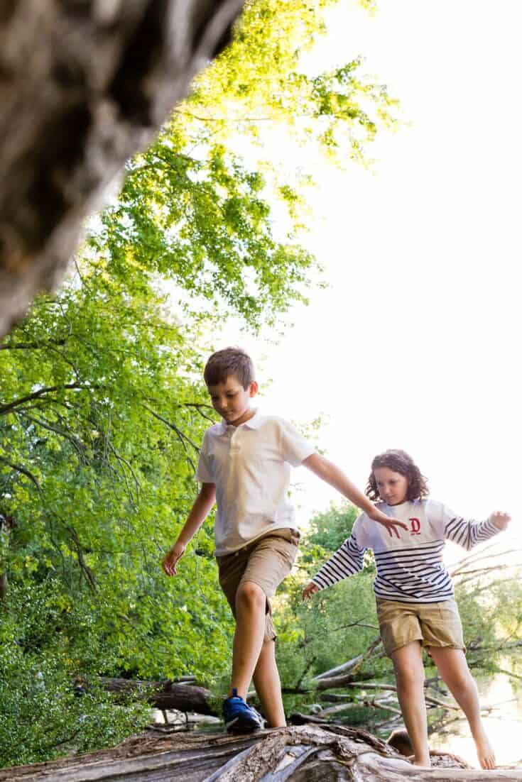 boy and girl balancing and walking on a log outside