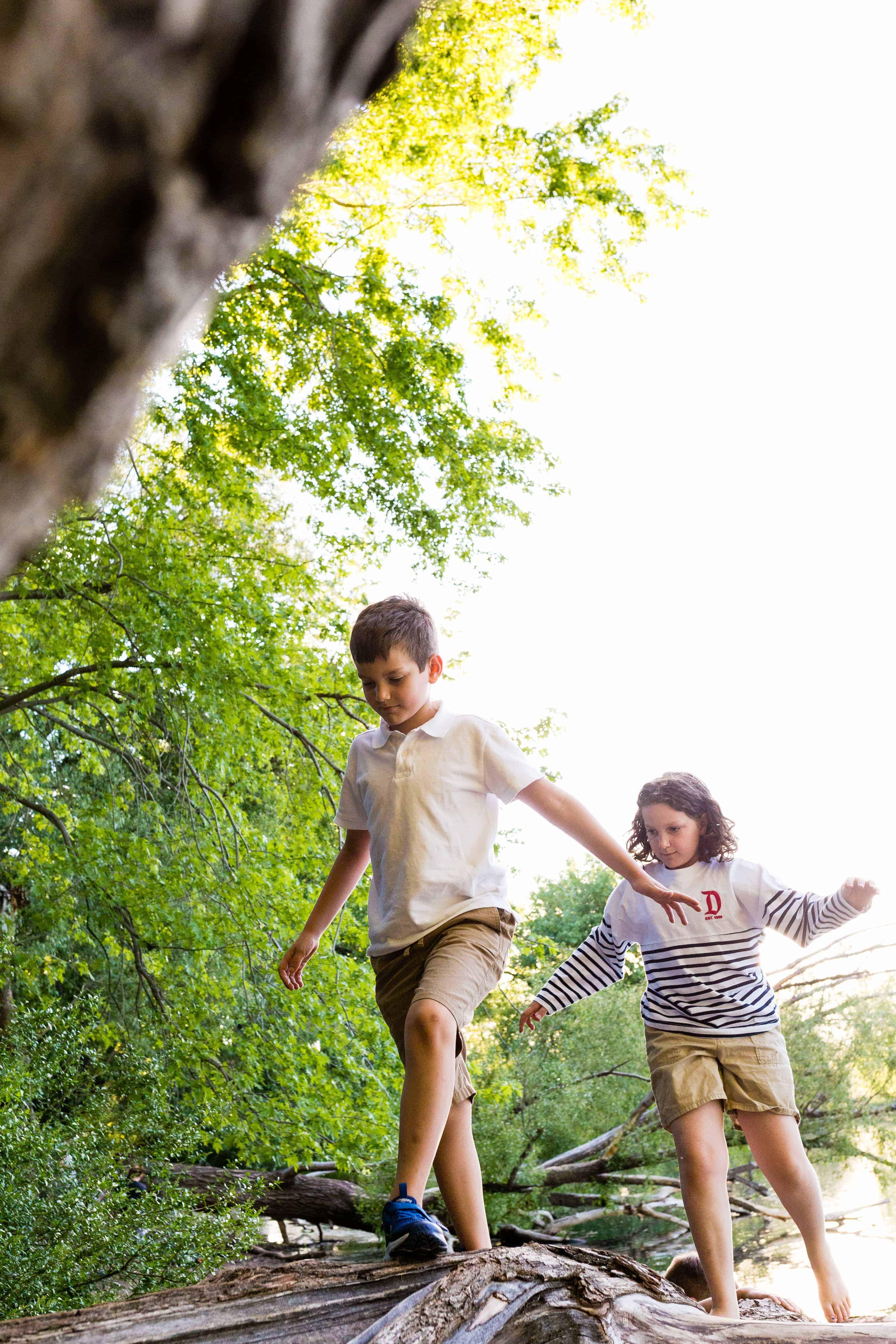 boy and girl balancing and walking on a log outside