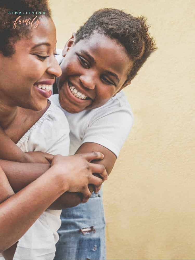 child hugging mom from behind while smiling _ Parenting teens during a crisis