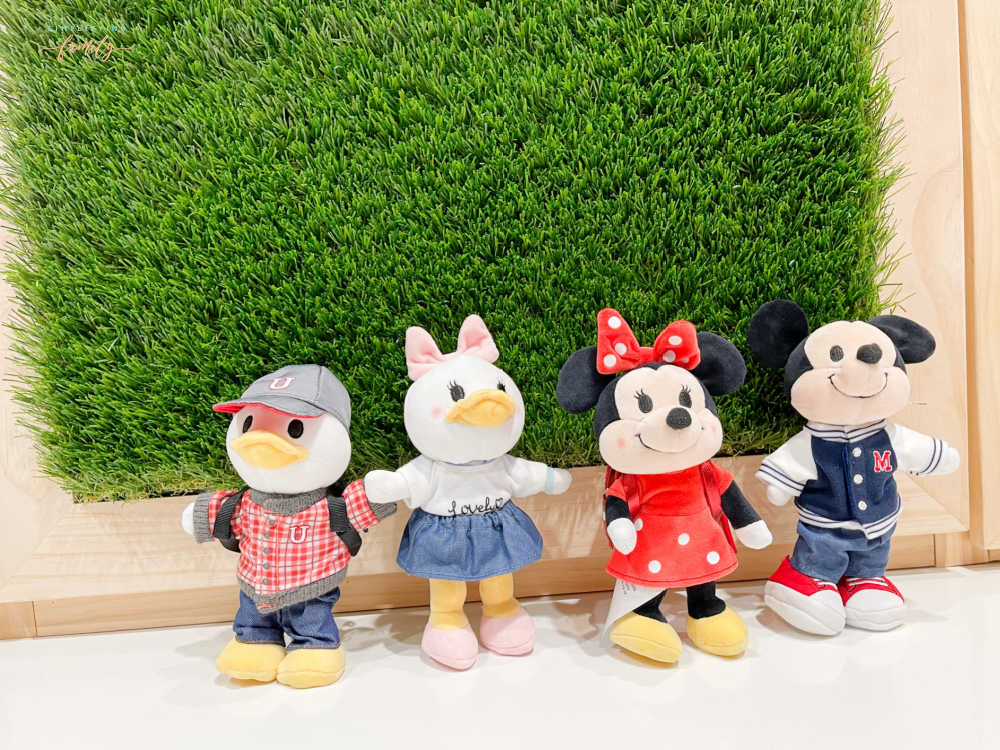 Disney's Mickey Mouse, Minnie Mouse, Donald Duck, and Daisy Duck Disney nuiMOs in front of grass wall with wood frame