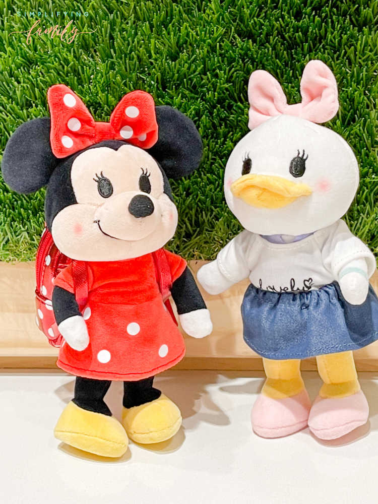Disney's Minnie Mouse, and Daisy Duck Disney nuiMOs with Loungefly backpack in front of green grass wall with wood frame